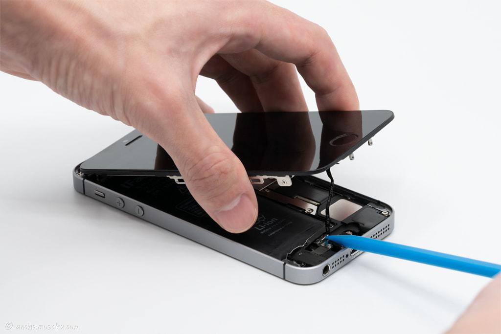 iPhone SE バッテリー交換手順: ヘラ(棒状)の鋭角側で本体側のホームボタンケーブルのコネクタカバーを浮かせる
