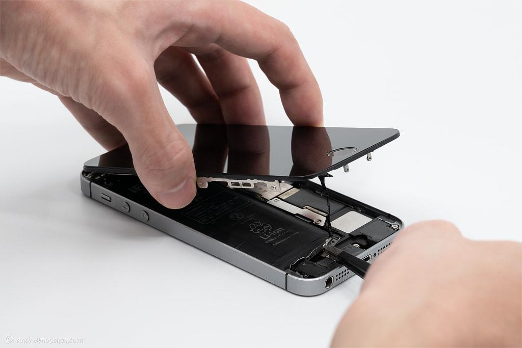 iPhone SE バッテリー交換手順: ピンセット(絶縁)を使い、ホームボタンケーブルのコネクタカバーを取り外す