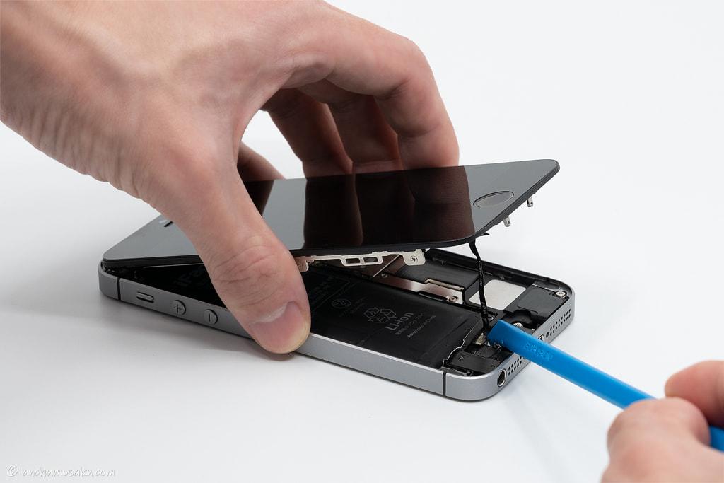 iPhone SE バッテリー交換手順: ヘラ(棒状)の平面側でホームボタンケーブルのコネクタを外す