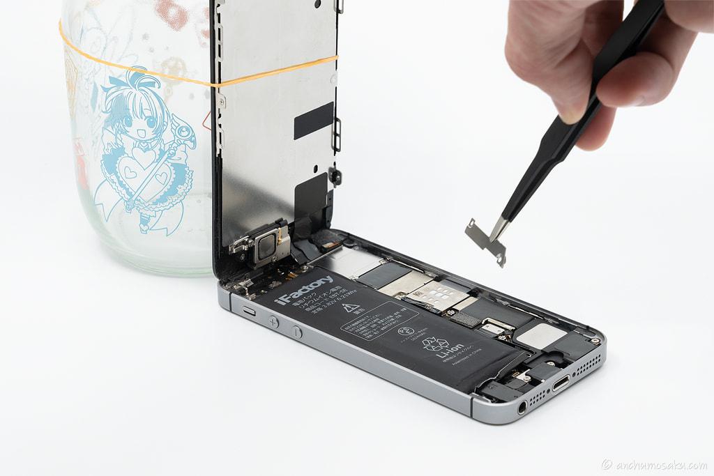iPhone SE バッテリー交換手順: ピンセット(絶縁)でバッテリーコネクタの保護プレートを取り外す